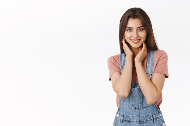 Attractive alluring brunette woman in dungarees, t-shirt touching her neck and smiling with gentle coquettish expression, standing seductive, self-accepting own body and beauty, white background