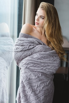 Attractive alluring young female with beautiful long hair in grey coverlet looking through the window