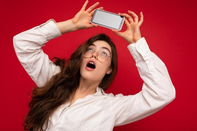 Привлекательная изумленная молодая брюнетка женщина в белой рубашке и оптических очках, изолированных на красном