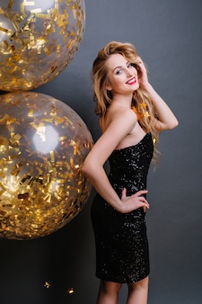 Attractive amazing woman from back in luxury black dress, with long curly blonde hair, red lips smiling with big balloons full with golden tinsels. celebrating, party.
