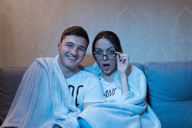 Привлекательные и возбужденные молодой мальчик и девочка в очках, прижимаясь друг к другу под одеялом на диване дома, смотрят телевизор, вид спереди в синем сиянии от съемочной площадки