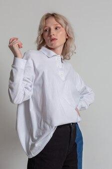 白い背景にポーズをとって白いシャツを着た魅力的でフェミニンな金髪の若い女性