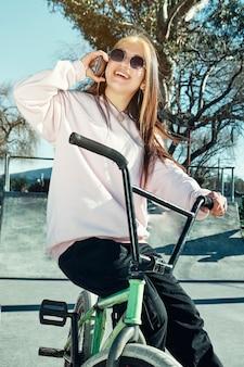魅力的で楽しい女の子が自転車に乗っている間、彼女の携帯電話で話している