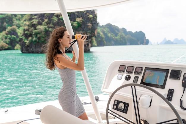 Привлекательная и великолепная брюнетка сидит и за рулем на современной яхте