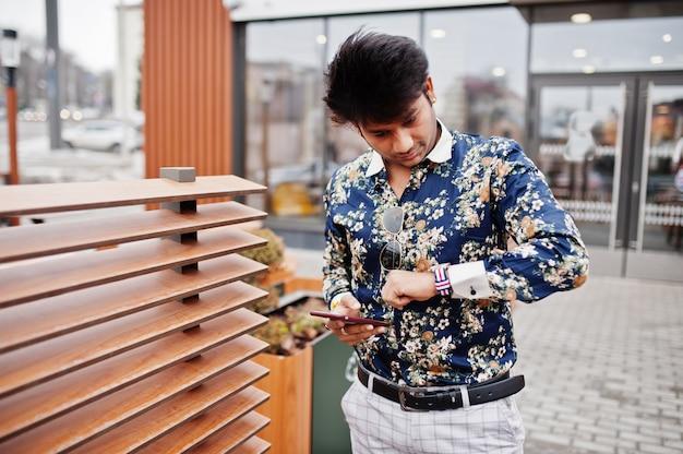 魅力的でハンサムなスタイリッシュな男がシャツを着て、携帯電話を保持し、時計を見て、休憩時にモダンなラウンジカフェのテラスに立っています。