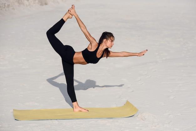 日の出や日没のビーチでの演習を行う魅力的で健康的な若い女性。ヨガマットの上でストレッチをしているフィットネス女の子。健康的なライフスタイルのコンセプトです。