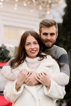 Привлекательный и любящий мужчина и девушка обнимаются с красным ретро-автомобилем, концепция рождественской истории любви
