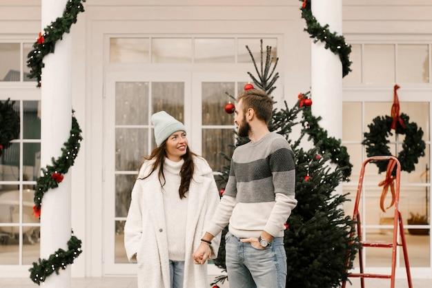 Привлекательный и любящий мужчина и девушка с красным ретро-автомобилем, концепция рождественской истории любви