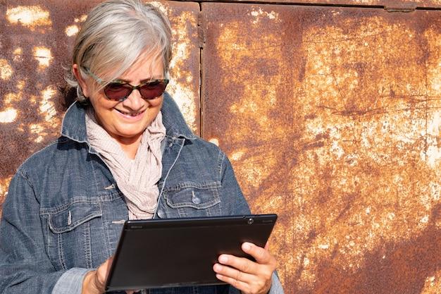 매력적이고 현대적인 노인 여성은 태양 아래 야외에서 디지털 태블릿을 사용하여 회색 머리를 하고 있습니다. 건설 현장의 녹슨 금속 패널의 배경