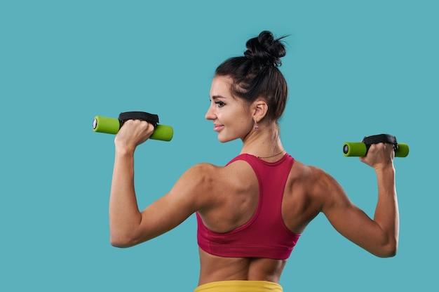 매력적이고 근육질의 젊은 여성이 아령으로 펌핑하면서 등 근육을 보여줍니다.