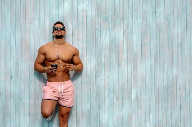 체육관에서 벽에 기대어 매력적이 고 근육 질의 젊은 남자