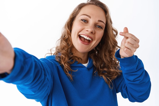 손가락 하트 사인으로 셀카를 찍는 매력적이고 긍정적인 소녀, 행복한 미소, 뻗은 손, 흰 벽으로 스마트폰 카메라를 들고