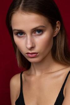 暗赤色の背景に魅力的で深刻なブルネットの女性のクローズアップの肖像画