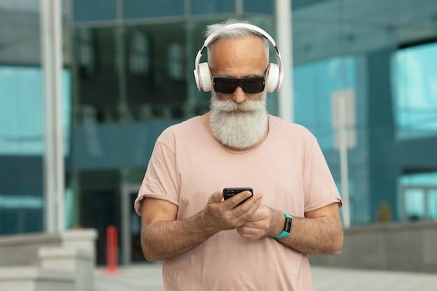 Привлекательный и улыбающийся бородатый старик с белыми волосами, наслаждающийся музыкой со смартфона на открытом воздухе в белых наушниках.