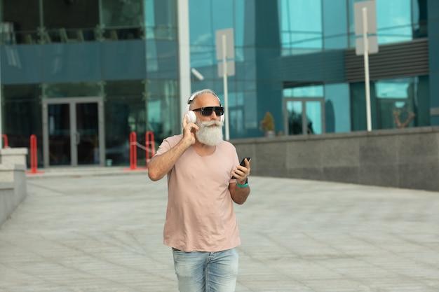 白いヘッドフォンを身に着けている屋外のスマートフォンから音楽を楽しんでいる白い髪の魅力的で笑顔のひげを生やした老人。