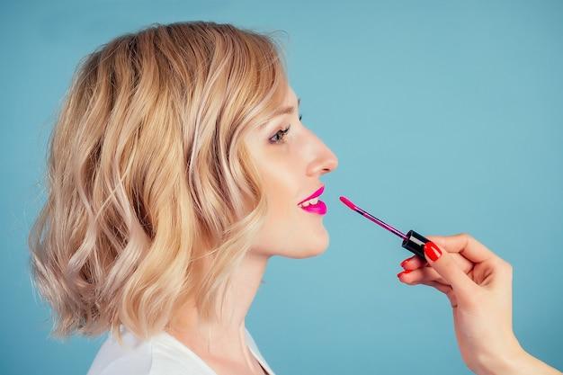 Привлекательная и улыбающаяся блондинка женщина применяет помаду для губ розового цвета фуксии в студии на синем фоне