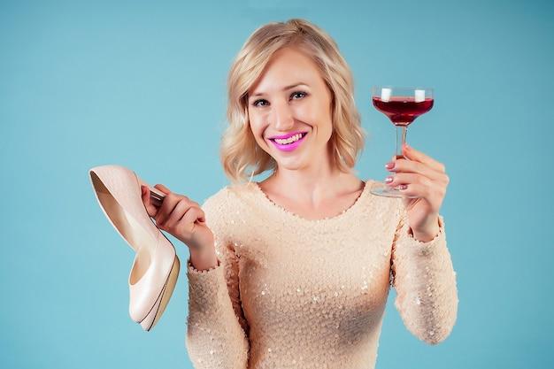 Привлекательные и улыбающиеся блондинки шикарный макияж лица женского пола в вечернем коктейльном платье, держа бокал красного вина и туфли на высоких каблуках в студии на синем фоне. понятие партии и алкоголизма