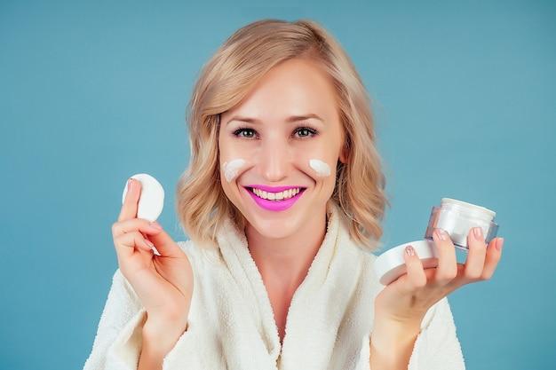 면 흰색 목욕 가운을 입은 매력적이고 웃는 금발 여성은 파란색 배경에 있는 스튜디오의 얼굴에 모이스처라이저 크림을 바릅니다. 스킨 케어 및 스파의 개념