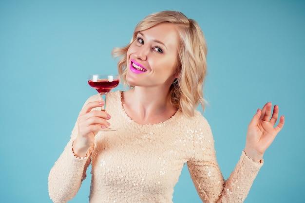 Привлекательная и улыбающаяся блондинка шикарный макияж и прическа в вечернем коктейльном платье, держа бокал красного вина в студии на синем фоне. концепция партии 2019 новый год.