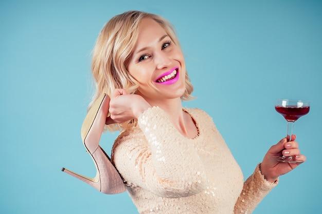 Привлекательная и улыбающаяся блондинка шикарный макияж в вечернем коктейльном платье, держа бокал красного вина и туфли на высоком каблуке в студии на синем фоне. концепция вечеринки и праздника