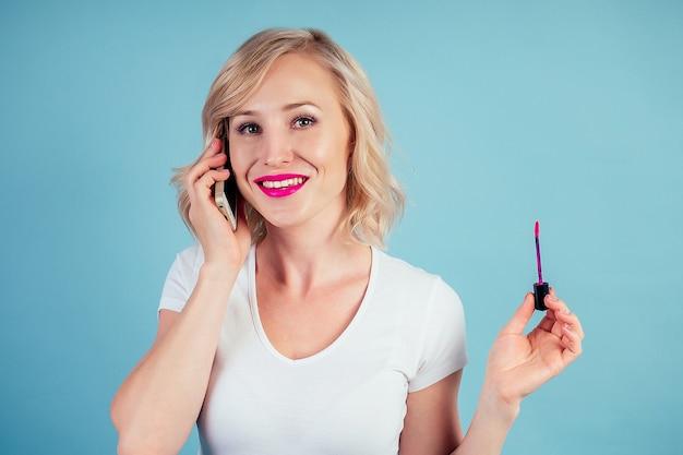 Привлекательная и улыбающаяся женщина-блондинка применяет помаду для губ розового цвета фуксии в студии на синем фоне
