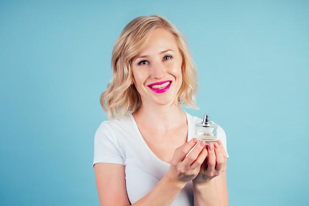 Привлекательная и улыбающаяся женщина блондинка держит флакон духов в студии на синем фоне
