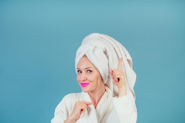 면 흰색 목욕 가운과 머리에 수건 터번을 입은 매력적이고 웃는 여성은 파란색 배경 카피스페이스에 있는 스튜디오의 위쪽을 가리킵니다. 스파와 여성 위생의 개념