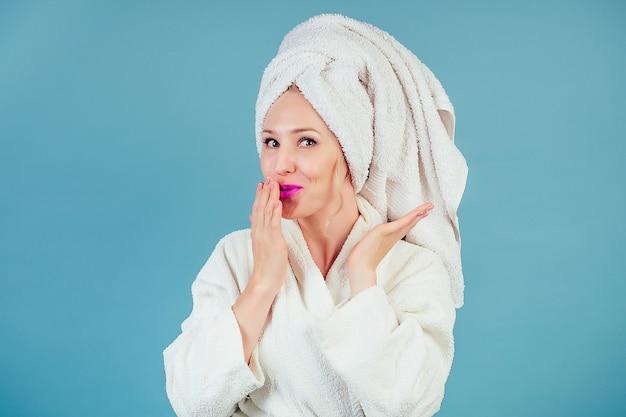 파란색 배경에 스튜디오의 머리에 면 흰색 목욕 가운과 수건 터번을 입은 매력적이고 웃는 와우 여성. 스파 및 신선도 여성 위생의 개념