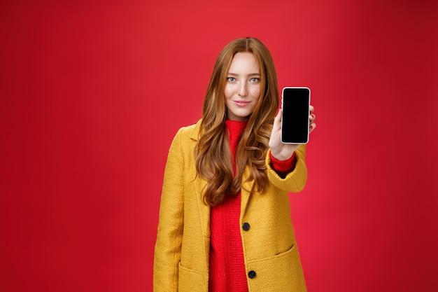 자신감이 있는 매력적이고 세련된 생강 소녀. 스마트폰 화면이 빨간색 배경에 대해 포즈를 취하면서 기뻐하며 웃고 있는 스마트폰 화면을 보여주는 카메라에서 휴대폰을 당기는 시선과 자신감 넘치는 미소.