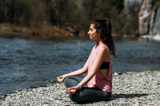 Привлекательная и молодая женщина занимается йогой у реки на рассвете, крупным планом. йога на свежем воздухе. счастливая женщина делает упражнения йоги. медитация на природе. женщина занимается йогой у реки. копировать пространство