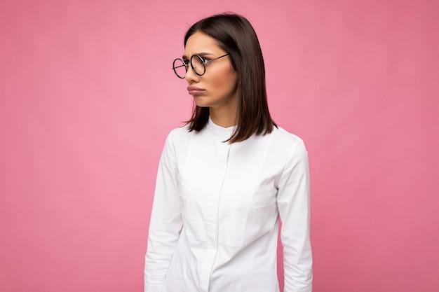 Привлекательная злая спрашивающая молодая брюнетка женщина в повседневной стильной одежде и современных оптических очках