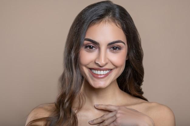魅力的な外観。素敵な歯を見せる笑顔と首の近くで彼女の指に触れる裸の肩を持つうれしそうな若い女性