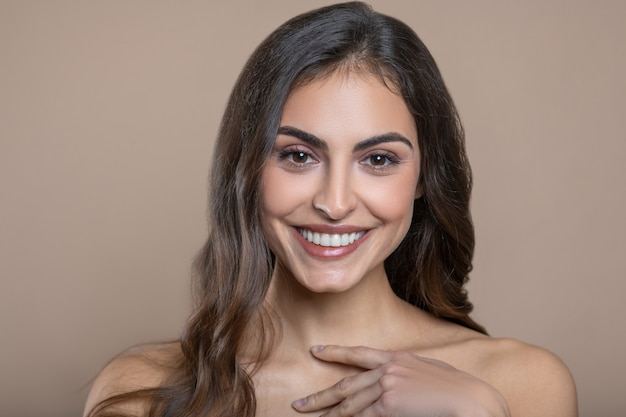 Attractive appearance. joyful young woman with lovely toothy smile and bare shoulders touching her fingers near neck