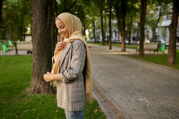 夏の公園でポーズをとるヒジャーブの魅力的なアラブの女の子。大学のキャンパスの芝生で休んでいるイスラム教徒の女性。