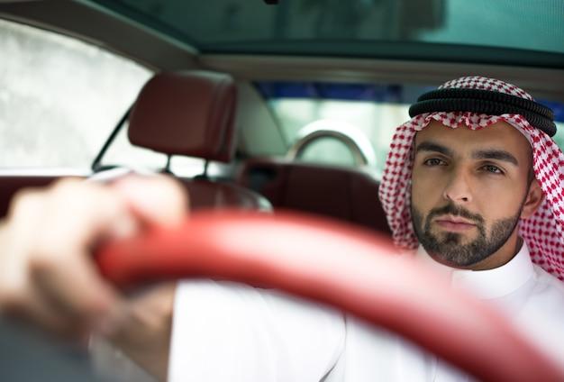 通りに車で魅力的なアラブの男