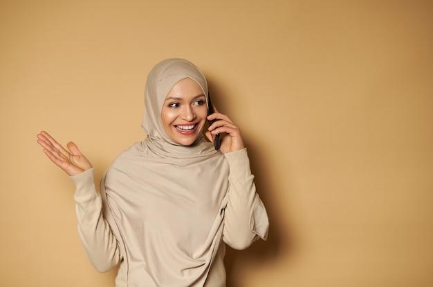 コピースペースでベージュの表面に立って携帯電話で話している美しい歯を見せる笑顔と覆われた頭を持つ魅力的なアラブの女性