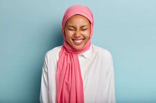 Attraente donna araba ride con un ampio sorriso, tiene gli occhi chiusi, esprime buone emozioni