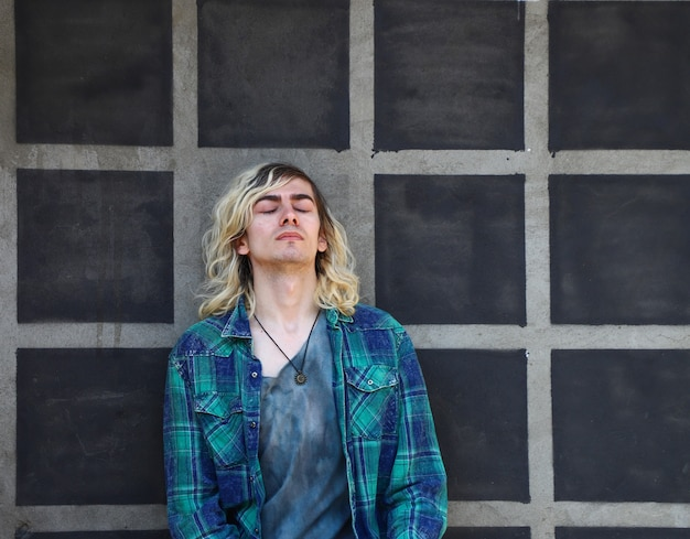 Attraente ragazzo armeno appoggiato a un muro grigio con gli occhi chiusi
