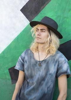 Attraente ragazzo armeno con un cappello appoggiato su un muro blu e verde e guardando lontano