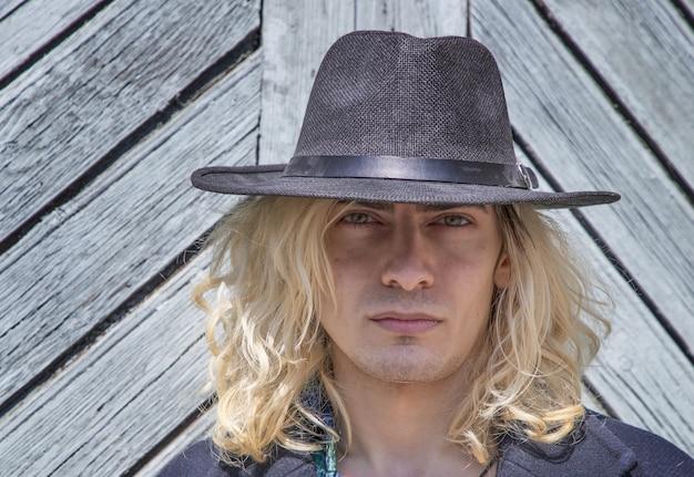 Attraente ragazzo armeno con un cappello appoggiato su una parete di legno grigia mentre guarda la telecamera