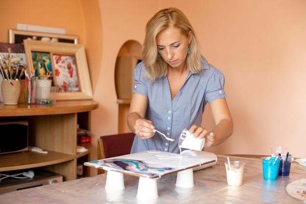Привлекательная художница вдохновенно работает над созданием картины в своей творческой мастерской. творчество и дизайн. современная живопись. интерьерные картины. мастер-класс по созданию интерьерных картин.