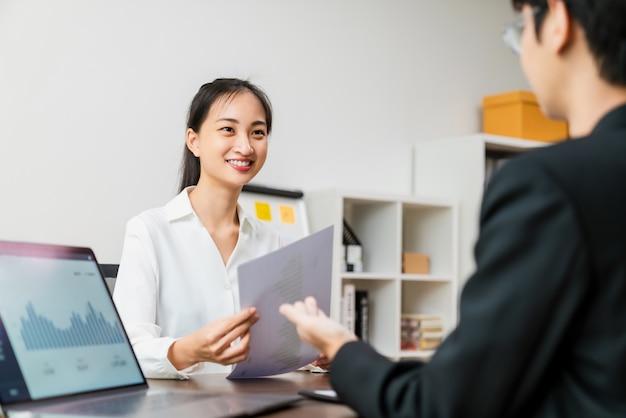 Привлекательная азиатская деловая встреча встречается и разговаривает для мозгового штурма о планировании совместной работы на столе с ноутбуком в офисе.