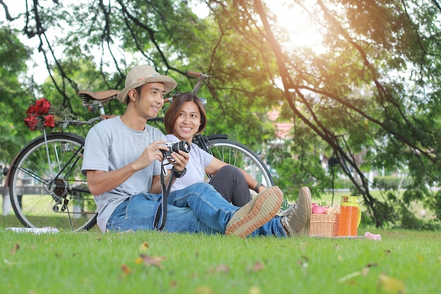 公園の共存のリラクゼーションコンセプトで魅力的なアジアカップル