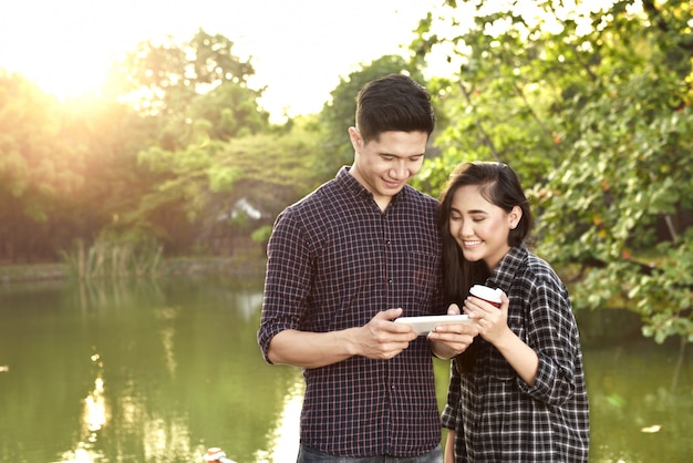 Attractive asian couple with tablet on the park