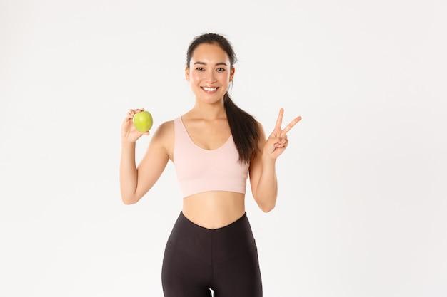 Привлекательный азиатский женский фитнес-тренер, девушка-тренер советует есть здоровую пищу после тренировки и тренировки, стоя с яблоком, показывает знак мира.