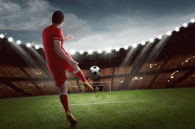 魅力的なアジアのフットボール選手がゴールにボールを撃つ