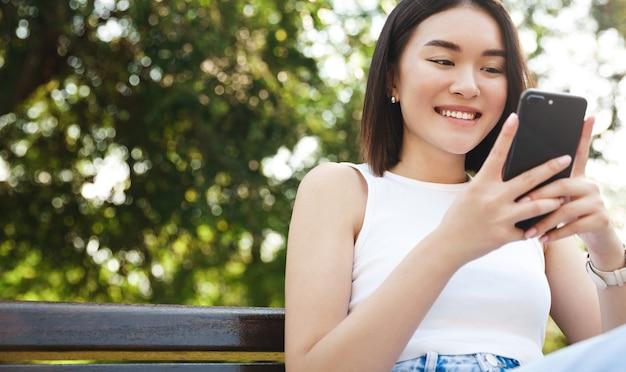 매력적인 아시아 여자 스마트 폰 들고 공원에서 문자 메시지를 읽고