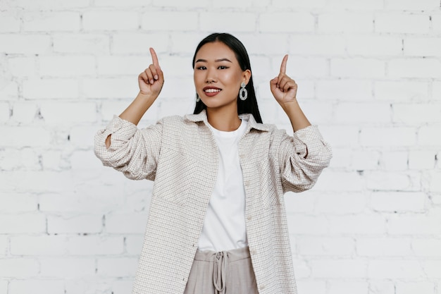 Attractive asian lady in beige cardigan points fingers up at place for text