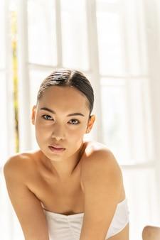 카메라에 포즈 흰색 탑에 매력적인 아시아 여자