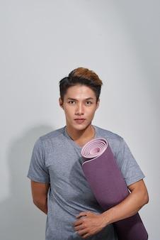 스튜디오에서 포즈를 취하는 요가 매트를 가진 매력적인 아시아 남자
